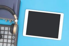 Κενή ταμπλέτα με το ακουστικό και βασικό μαξιλάρι του DJ στο μπλε backgr Στοκ Εικόνες