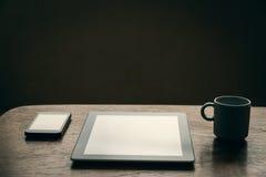 Κενή ταμπλέτα, κενό smartphone και καυτό φλιτζάνι του καφέ στον ξύλινο πίνακα Στοκ Φωτογραφία