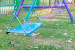 Κενή ταλάντευση αλυσίδων και μετάλλων στον τομέα χλόης παιδικών χαρών και λιβαδιών Στοκ φωτογραφίες με δικαίωμα ελεύθερης χρήσης