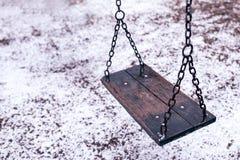 Κενή ταλάντευση στην παιδική χαρά παιδιών κάτω από το χιόνι Στοκ Εικόνες