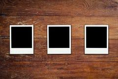Κενή φωτογραφία πλαισίων στο ξύλινο υπόβαθρο Στοκ Φωτογραφίες