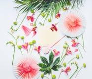 Κενή χλεύη ευχετήριων καρτών επάνω με τους ανεμιστήρες κομμάτων εγγράφου, τα τροπικά φύλλα και τα εξωτικά λουλούδια στο άσπρο υπό στοκ εικόνα με δικαίωμα ελεύθερης χρήσης