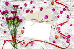 Κενοί άσπροι ευχετήρια κάρτα και φάκελος με τα λουλούδια και την κόκκινη κορδέλλα Στοκ Εικόνες