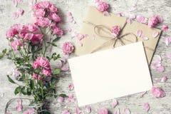 Κενοί άσπροι ευχετήρια κάρτα και φάκελος με τα ρόδινα ροδαλά λουλούδια Στοκ φωτογραφία με δικαίωμα ελεύθερης χρήσης