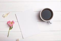 Κενοί έγγραφο, καφές και λουλούδι στον άσπρο πίνακα στοκ φωτογραφίες