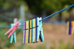 Κενοί ζωηρόχρωμοι γόμφοι ενδυμάτων στη σειρά στον κήπο Στοκ Φωτογραφίες