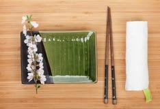 Κενοί πιάτο, chopsticks και κλάδος sakura Στοκ φωτογραφία με δικαίωμα ελεύθερης χρήσης