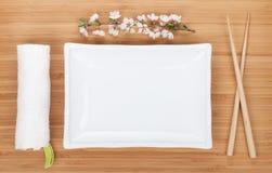 Κενοί πιάτο, chopsticks και κλάδος sakura Στοκ εικόνες με δικαίωμα ελεύθερης χρήσης