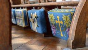 Κεντημένα μαξιλάρια προσευχής Kneelers που κρεμούν από τον πάγκο εκκλησιών στοκ φωτογραφίες με δικαίωμα ελεύθερης χρήσης