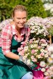 Κεντρική γυναίκα κήπων που κρατά το σε δοχείο χαμόγελο λουλουδιών Στοκ εικόνα με δικαίωμα ελεύθερης χρήσης