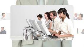 Κεντρικοί πράκτορες κλήσης που εργάζονται μαζί στα γραφεία τους απόθεμα βίντεο