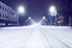 Κεντρικός δρόμος με τα αυτοκίνητα και το χιόνι τη νύχτα Στοκ Φωτογραφία