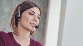 Κεντρικός πράκτορας κλήσης που εργάζεται στο φωτεινό γραφείο που μιλά με την κάσκα απόθεμα βίντεο