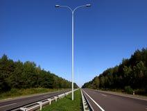 Κενός δρόμος και η σειρά των συσκευών φωτισμού Στοκ Φωτογραφίες