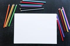 Κενός κατάλογος εγγράφου με τα χρωματισμένα μολύβια γύρω στο μαύρο πίνακα κιμωλίας στοκ εικόνες