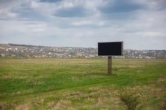 Κενός μαύρος πίνακας διαφημίσεων με το πρότυπο για τη διαφήμιση στη μέση του πράσινου τομέα στοκ φωτογραφίες
