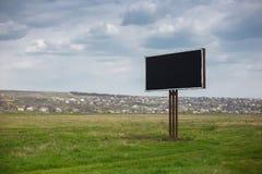 Κενός μαύρος πίνακας διαφημίσεων με το πρότυπο για τη διαφήμιση στη μέση του πράσινου τομέα στοκ εικόνες