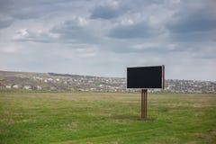Κενός μαύρος πίνακας διαφημίσεων με το πρότυπο για τη διαφήμιση στη μέση του πράσινου τομέα στοκ φωτογραφία με δικαίωμα ελεύθερης χρήσης