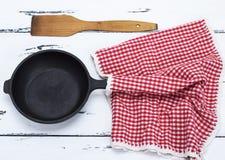 Κενός μαύρος στρογγυλός χυτοσίδηρος που τηγανίζει την παν και κόκκινη πετσέτα Στοκ εικόνα με δικαίωμα ελεύθερης χρήσης