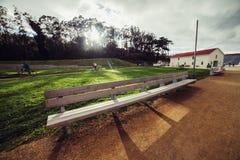 Κενός ξύλινος πάγκος στο πάρκο πόλεων στο χρόνο ηλιοβασιλέματος Χρυσό πάρκο πυλών του Σαν Φρανσίσκο Στοκ φωτογραφία με δικαίωμα ελεύθερης χρήσης