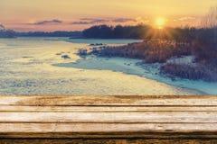 Κενός ξύλινος πίνακας με το θολωμένο picteresque χειμερινό υπόβαθρο της όχθης ποταμού στο ηλιοβασίλεμα Χλεύη επάνω για την επίδει στοκ φωτογραφία