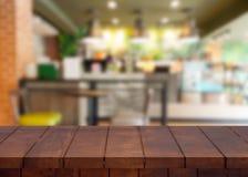 Κενός ξύλινος τοπ πίνακας και θολωμένο υπόβαθρο καφετεριών στοκ φωτογραφία