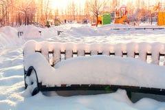 Κενός ξύλινος χιονισμένος πάγκος στη πλατεία της πόλης στοκ φωτογραφία με δικαίωμα ελεύθερης χρήσης