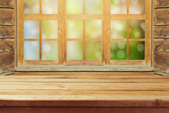 Κενός ξύλινος αγροτικός πίνακας πέρα από το παράθυρο και το πράσινο υπόβαθρο bokeh Στοκ εικόνες με δικαίωμα ελεύθερης χρήσης