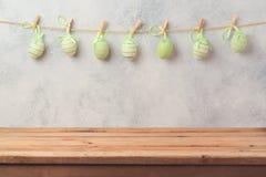 Κενός ξύλινος πίνακας γεφυρών πέρα από το αγροτικό υπόβαθρο τοίχων με τη γιρλάντα διακοσμήσεων αυγών όμορφος λεκές διακοπών αυγών Στοκ Φωτογραφίες
