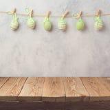 Κενός ξύλινος πίνακας γεφυρών πέρα από το αγροτικό υπόβαθρο τοίχων με τη γιρλάντα διακοσμήσεων αυγών όμορφος λεκές διακοπών αυγών Στοκ Εικόνα