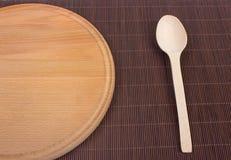 Κενός ξύλινος τέμνων πίνακας Ξύλινα κουτάλια και ξύλινα πιάτα Στοκ Εικόνες