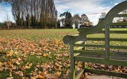 Κενός πάγκος πάρκων που βλέπει σε ένα δημόσιο πάρκο, κοντά σε μια πίσσα ποδοσφαίρου, που βλέπει το χειμώνα στοκ εικόνες