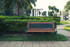 Κενός πάγκος που απομονώνεται σε ένα δημόσιο πάρκο με τον κήπο στοκ φωτογραφία
