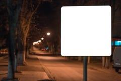 Κενός πίνακας διαφημίσεων προτύπων για τη διαφήμιση της αφίσας κοντά στον κενό δρόμο στη νύχτα Δέντρα στο υπόβαθρο στοκ εικόνες