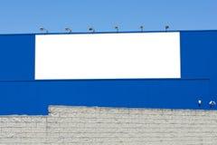 Κενός πίνακας διαφημίσεων στο τούβλο και τον μπλε τοίχο, την άκρη εμβλημάτων και τα στρόφια που συντηρούνται στοκ εικόνες