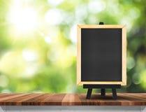 Κενός πίνακας στην ξύλινη επιτραπέζια κορυφή με το πράσινο δέντρο ήλιων και θαμπάδων Στοκ φωτογραφία με δικαίωμα ελεύθερης χρήσης