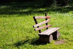 Κενός παλαιός ξύλινος πάγκος σε έναν πράσινο χορτοτάπητα Ηλιόλουστη ημέρα, κήπος ή ισοτιμία Στοκ φωτογραφία με δικαίωμα ελεύθερης χρήσης