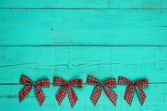 Κενός παλαιός μπλε ξεπερασμένος ξύλινος τοίχος κιρκιριών με τα κόκκινα σύνορα τόξων Χριστουγέννων καρό στοκ φωτογραφία με δικαίωμα ελεύθερης χρήσης