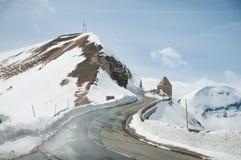 Κενός δρόμος που οδηγεί μέσω της φυσικών επαρχίας, του χιονιού & της ομίχλης στο βουνό Grossglockner, Αυστρία Στοκ Εικόνα