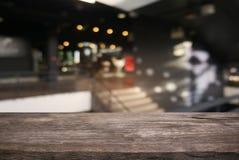 Κενός σκοτεινός ξύλινος πίνακας μπροστά από θολωμένο το περίληψη υπόβαθρο στοκ εικόνες με δικαίωμα ελεύθερης χρήσης