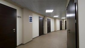 Κενός, στρογγυλός διάδρομος με τους ελαφριούς μπεζ τοίχους και τις κλειστές, σκοτεινές καφετιές πόρτες Κλειστές πόρτες κατά μήκος απόθεμα βίντεο