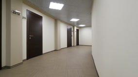 Κενός, στρογγυλός διάδρομος με τους ελαφριούς μπεζ τοίχους και τις κλειστές, σκοτεινές καφετιές πόρτες Κλειστές πόρτες κατά μήκος φιλμ μικρού μήκους