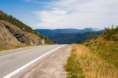 Κενός στρωμένος ώμος δρόμων και αμμοχάλικου ενάντια στους λόφους και τα βουνά Στοκ Εικόνα