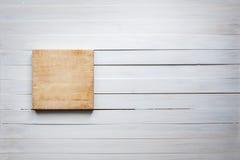 Κενός τέμνων πίνακας στην εκλεκτής ποιότητας άσπρη ξύλινη έννοια υποβάθρου τροφίμων πινάκων Στοκ Εικόνες