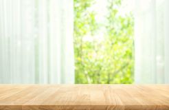 Κενός της ξύλινης επιτραπέζιας κορυφής στη θαμπάδα της κουρτίνας με την άποψη παραθύρων πράσινη από το υπόβαθρο κήπων δέντρων στοκ εικόνα με δικαίωμα ελεύθερης χρήσης