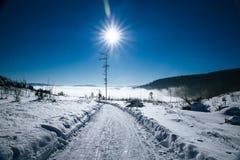 Κενός χιονώδης δρόμος και λάμποντας ήλιος Στοκ Εικόνα