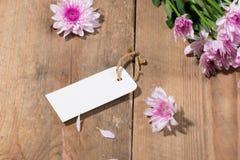 Κενό άσπρο έγγραφο ετικεττών με τα λουλούδια χρώματος στο ξύλινο υπόβαθρο Τ Στοκ Εικόνα