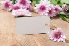 Κενό άσπρο έγγραφο ετικεττών με τα λουλούδια χρώματος στο ξύλινο υπόβαθρο Τ Στοκ εικόνες με δικαίωμα ελεύθερης χρήσης