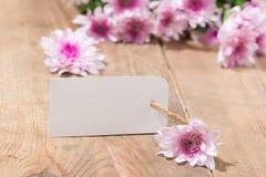 Κενό άσπρο έγγραφο ετικεττών με τα λουλούδια χρώματος στο ξύλινο υπόβαθρο Τ Στοκ φωτογραφία με δικαίωμα ελεύθερης χρήσης