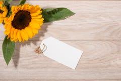 Κενό άσπρο έγγραφο ετικεττών με τα λουλούδια χρώματος στο ξύλινο υπόβαθρο Τ Στοκ εικόνα με δικαίωμα ελεύθερης χρήσης